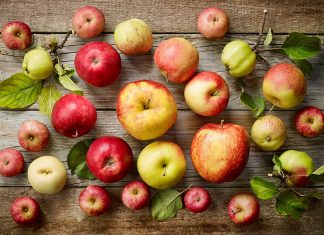 various kinds of fresh apples on wooden table, top view