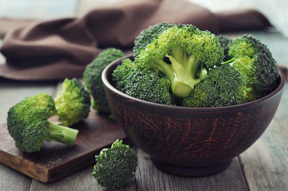 Bunch of fresh green broccoli in brown bowl over wooden background