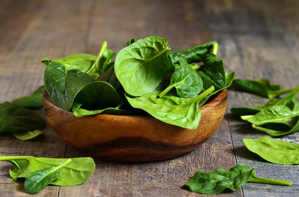 Spinach leaves in a wooden bowl on a wooden table.