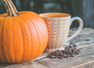 pumpkin on a table with a cup of coffee