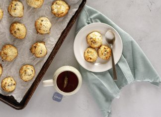 A plate and cookie sheet filed with coconut macaroons and a cup of tea.