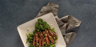 Square plate with sliced beef and broccolini.