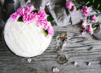 White cake with pink flowers on top.