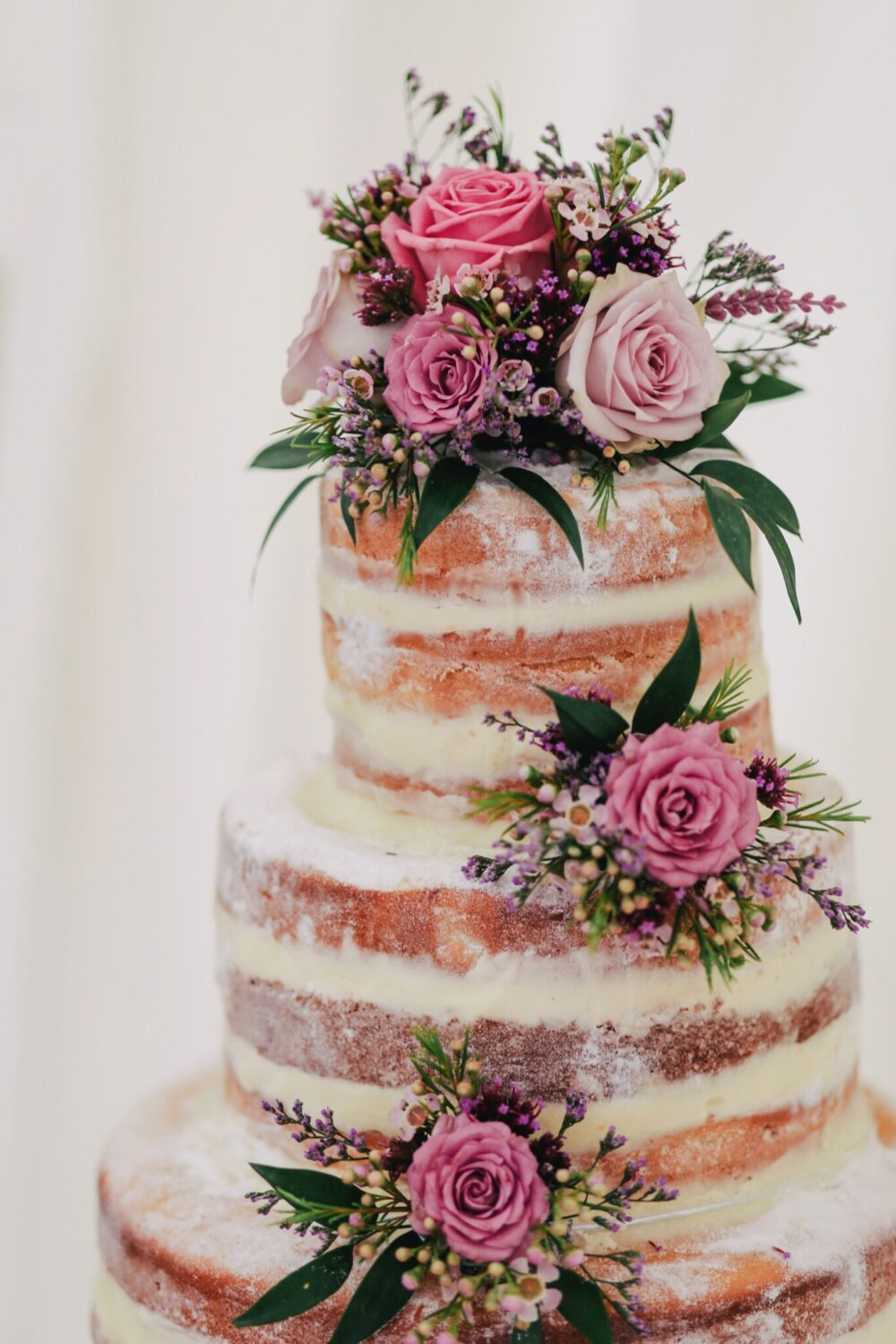 Layered cake decorated with edible flowers for cake.
