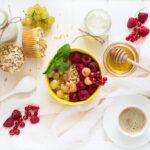 healthy breakfast muesli honey yogurt muffins coffee and fresh berries on white wooden background t20 neLdon